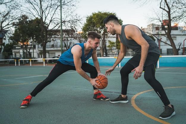 Portret van twee jonge vrienden die basketbal spelen en plezier hebben op het veld buiten. sport concept.