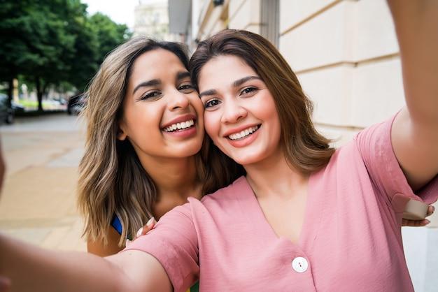 Portret van twee jonge vrienden die een selfie nemen terwijl ze buiten op straat staan