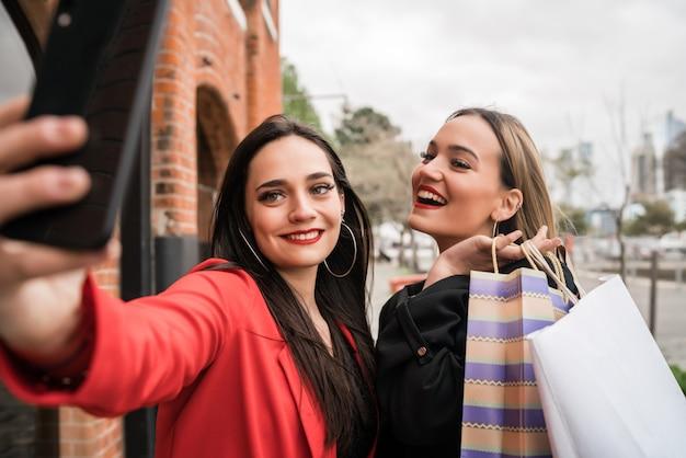 Portret van twee jonge vrienden die genieten van het samen winkelen tijdens het nemen van een selfie met telefoon op straat.