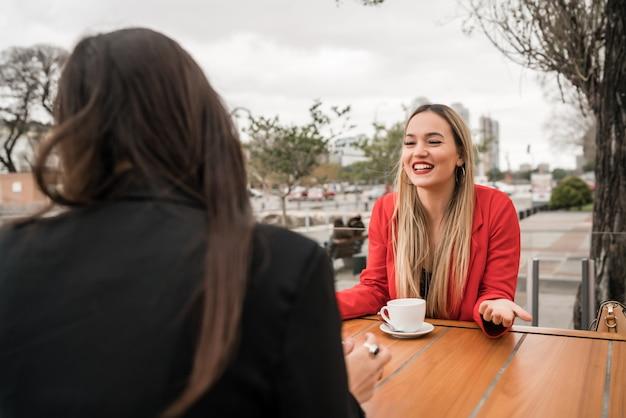 Portret van twee jonge vrienden die goede tijd samen doorbrengen terwijl u bij coffeeshop zit. levensstijl en vriendschapsconcept.