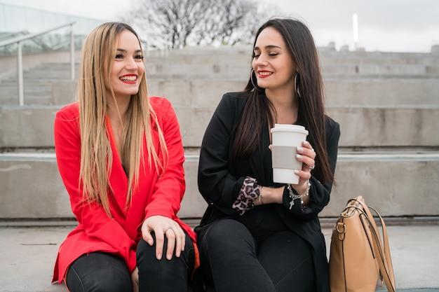 Portret van twee jonge vrienden die goede tijd samen doorbrengen terwijl ze buiten op straat zitten. levensstijl en vriendschapsconcepten.