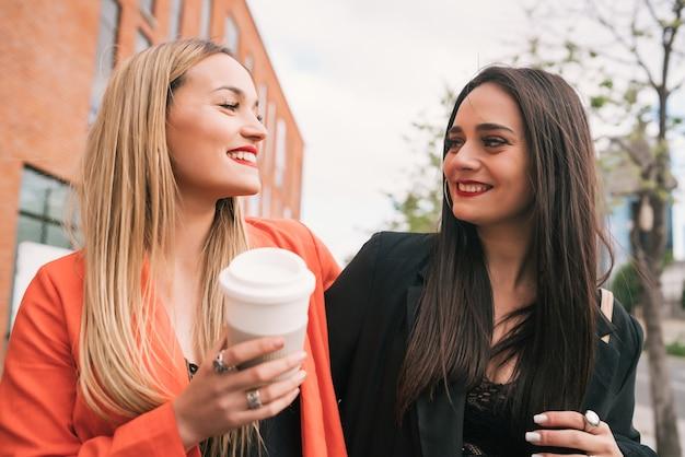 Portret van twee jonge vrienden die goede tijd samen doorbrengen tijdens het wandelen buiten op straat