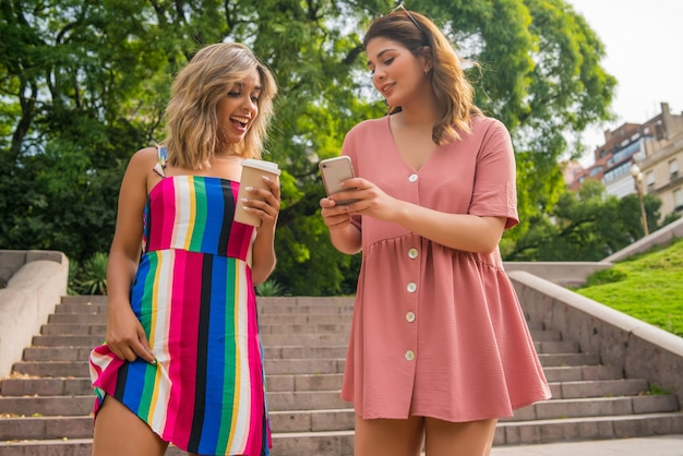 Portret van twee jonge vrienden die hun mobiele telefoon bekijken tijdens het buiten lopen