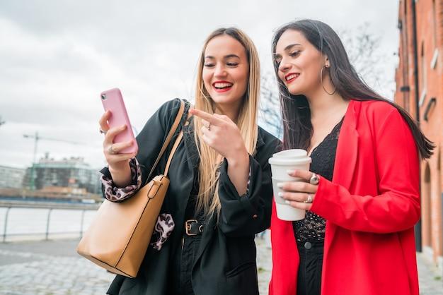 Portret van twee jonge vrienden die hun mobiele telefoon buiten op straat gebruiken. levensstijl en vriendschapsconcepten.
