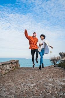 Portret van twee jonge vrienden die wat leuke tijd samen doorbrengen, langs kustlijn wandelen en plezier hebben.