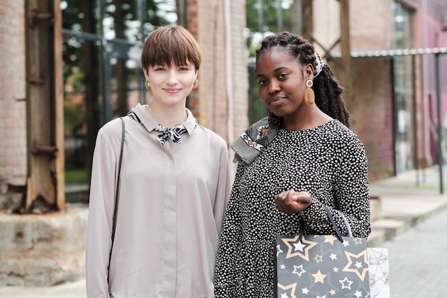 Portret van twee jonge vrienden met aankopen die naar de camera kijken terwijl ze een ontmoeting hebben in de stad