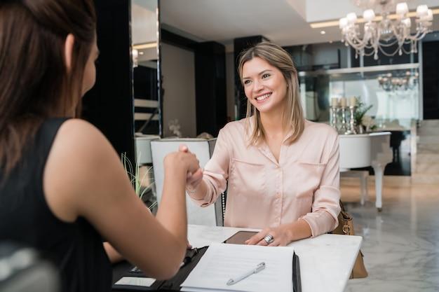 Portret van twee jonge vrouwelijke ondernemers die elkaar ontmoeten en handen schudden bij de lobby van het hotel. zakelijke reizen concept.