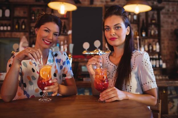 Portret van twee jonge vrouwen die cocktaildranken hebben