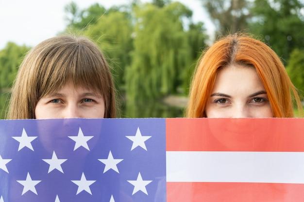 Portret van twee jonge vrouwen die hun gezichten achter de nationale vlag van de vs verbergen