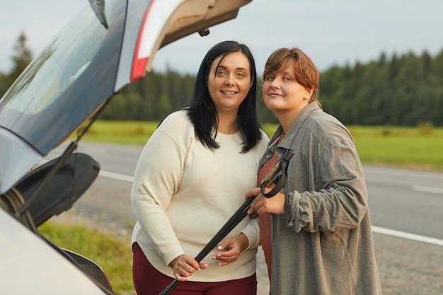 Portret van twee jonge vrouwen die op de weg staan en naar de camera glimlachen terwijl ze met de auto reizen