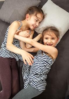 Portret van twee jonge zussen die elkaar op bed duwen