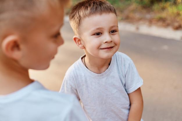 Portret van twee jongens, broers en zussen, broers en beste vrienden met witte casual t-shirts die buiten poseren, samen vrije tijd doorbrengen, kinderen die geluk uitdrukken.