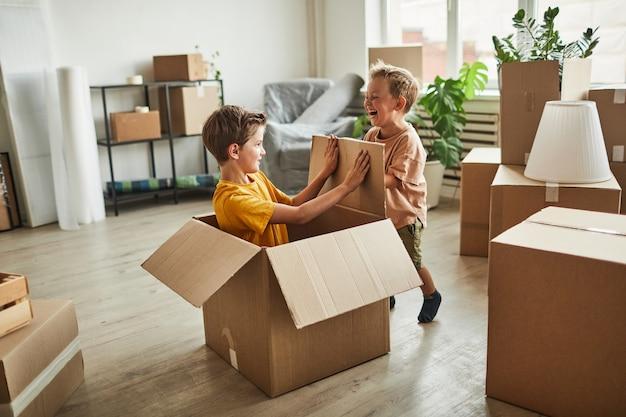 Portret van twee jongens die in kartonnen dozen spelen terwijl het gezin verhuist naar de kopieerruimte van een nieuw huis