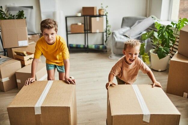 Portret van twee jongens die kartonnen dozen verplaatsen terwijl het gezin verhuist naar de kopieerruimte van een nieuw huis