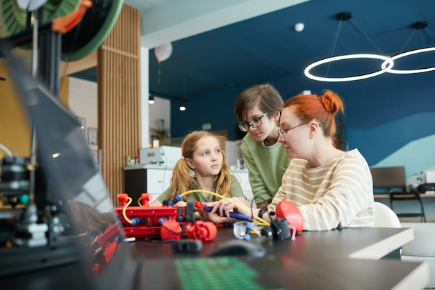 Portret van twee kinderen die een robot bouwen tijdens de technische les op school met een vrouwelijke leraar die helpt, kopieer ruimte