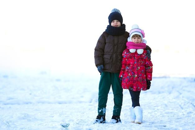 Portret van twee kinderen jongen en meisje buiten spelen in besneeuwde winterdag
