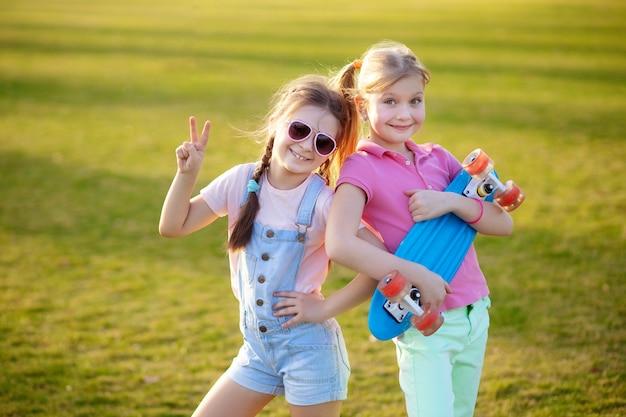 Portret van twee kleine gelukkige kinderen met een skateboard. buitensporten in het park.