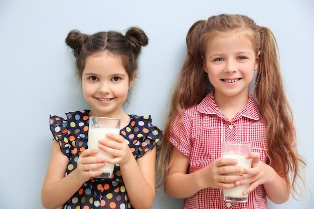Portret van twee kleine meisjes met glazen melk op blauw