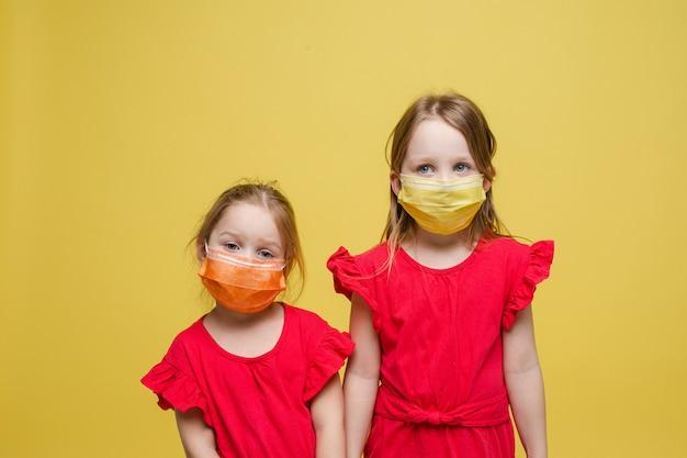 Portret van twee kleine meisjes met medische maskers op hun gezichten hebben een goede gezondheid, geïsoleerd op rode achtergrond