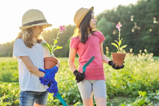 Portret van twee kleine mooie tuinders in hoedenhandschoenen met bloeiende planten in potten en tuinschoppen