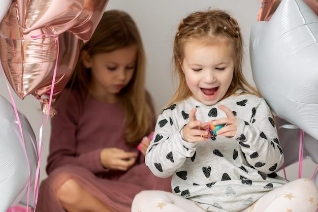 Portret van twee kleine schattige meisjes die op de vloer met ballons zitten