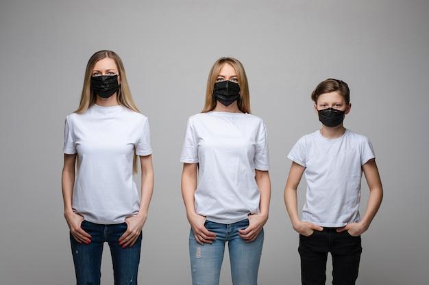 Portret van twee knappe meisjes met lang blond haar en een jonge jongen met zwarte medische maskers op hun gezichten die op grijze achtergrond worden geïsoleerd