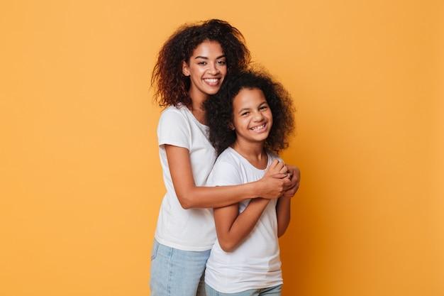 Portret van twee lachende afrikaanse zussen knuffelen