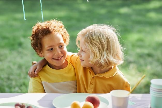 Portret van twee lachende jongens die elkaar omarmen aan een picknicktafel buiten terwijl ze genieten van een verjaardagsfeestje...