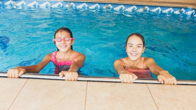Portret van twee lachende tienermeisjes in het zwembad
