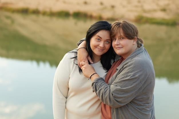 Portret van twee lesbiennes die elkaar omhelzen en camera bekijken tijdens het wandelen over de aard