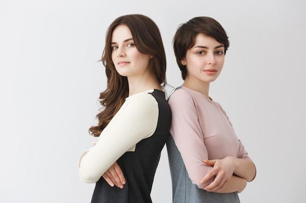 Portret van twee lesbische meisjes met donker haar glimlachen, rug naar elkaar staan, handen kruisen, poseren voor artikel over het leven van homo's.