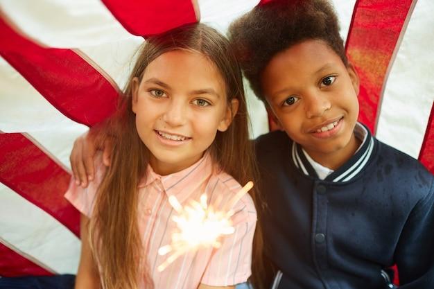 Portret van twee leuke meisjes die fonkelende lichten houden en op de vlag van de vs glimlachen