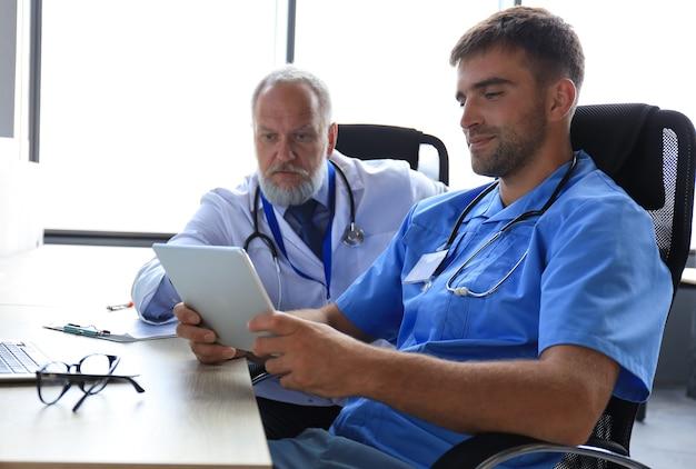 Portret van twee mannelijke artsen die digitale tablet gebruiken in een helder medisch kantoor.