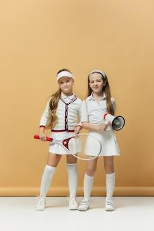 Portret van twee meisjes als tennisspelers die tennisracket houden.