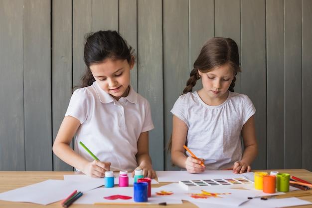 Portret van twee meisjes die op het witboek over het bureau schilderen
