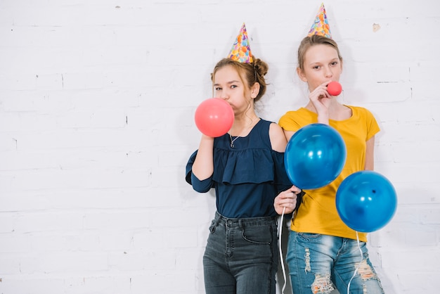 Portret van twee meisjes die rode ballons blazen die zich tegen de witte muur bevinden