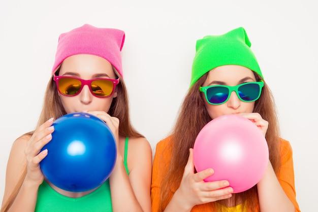 Portret van twee meisjes in hoeden en brillen die ballons blazen