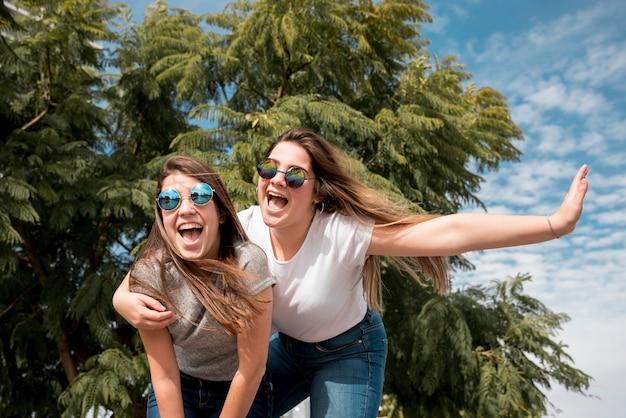 Portret van twee meisjes in stedelijke omgeving met plezier