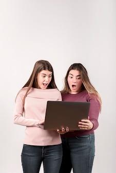 Portret van twee meisjes voor een muur