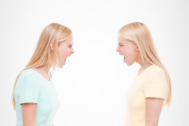 Portret van twee meisjes zweren. ge oleerd over witte muur.