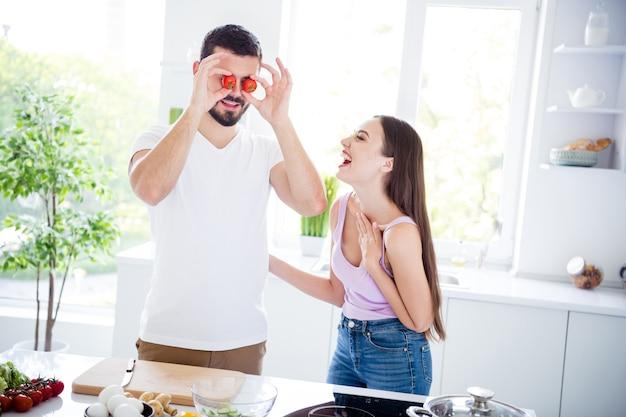 Portret van twee mensen bereiden vegetarische salade met plezier lachen