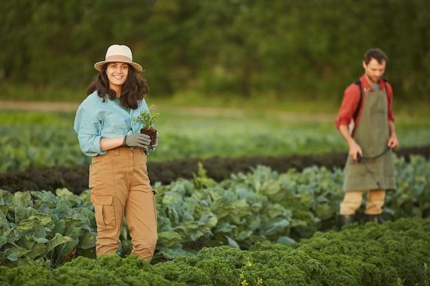 Portret van twee mensen die werkzaam zijn in het veld op de groenteplantage, focus op jonge vrouw die lacht op camera op voorgrond, kopieer ruimte