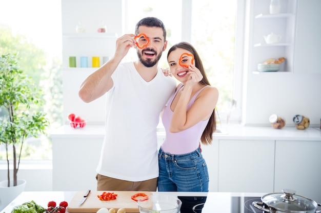 Portret van twee mensen positieve veganisten echtgenoten houden peper deksel oog