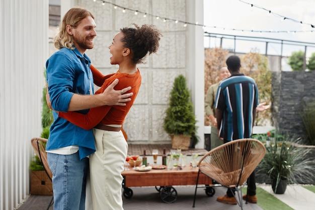 Portret van twee moderne jonge vrienden die elkaar begroeten op een feestje op het dak, kopieer ruimte