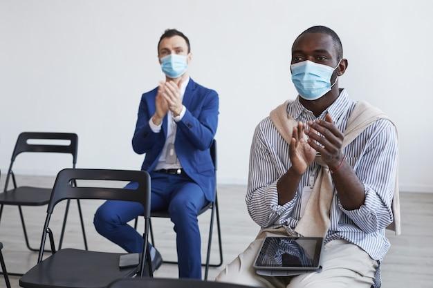 Portret van twee moderne zakenmensen die maskers dragen en applaudisseren met sociale afstand terwijl ze op stoelen in het publiek zitten tijdens een zakelijke conferentie of seminar