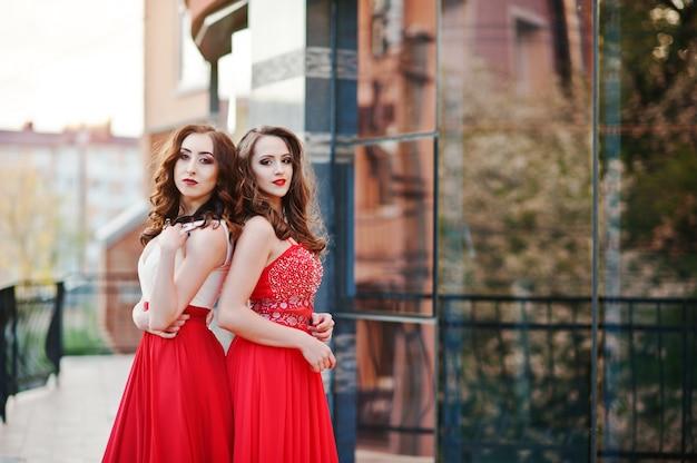 Portret van twee modieuze meisjes bij rode avondjurk gesteld achtergrondspiegelvenster van de moderne bouw