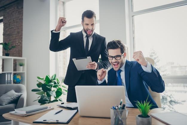 Portret van twee mooie aantrekkelijke knappe vrolijke vrolijke blije bekwame mannen expert econoom financier vieren doorbraak aanbesteding win geluk in licht wit interieur werkplek werkstation
