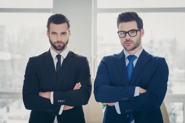 Portret van twee mooie aantrekkelijke zelfverzekerde serieuze imposante stijlvolle ervaren mannen deskundige voorzitter econoom advocatenkantoor eigenaar partnerschap oprichter gevouwen armen in licht wit interieur werkplek werkstation