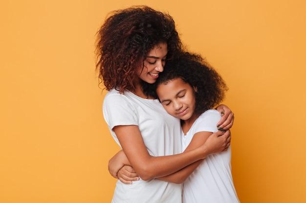 Portret van twee mooie afrikaanse zussen knuffelen