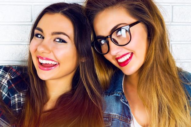 Portret van twee mooie en tienermeisjes die glimlachen stellen